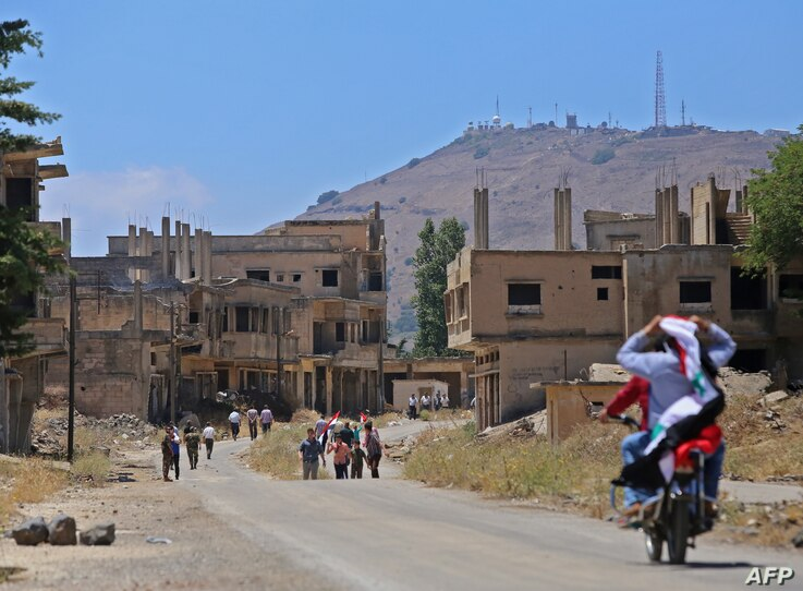 FILE - An Israeli military intelligence base (background) is pictured as Syrians return to the town of Quneitra in the Syrian Golan Heights, July 27, 2018.