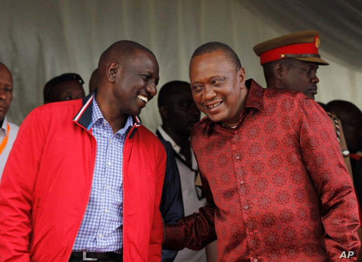 Kenyan President Uhuru Kenyatta (right) talks with Vice President William Ruto during the unveiling of a cargo train at the Mombasa, Kenya, port containers depot, May 30, 2017.