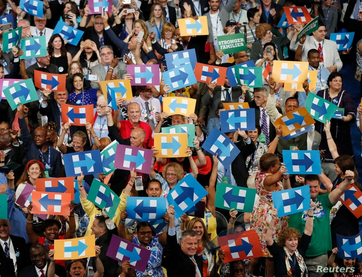 Delegates, including New York Mayor Bill de Blasio, hold Hillary Clinton signs after her nomination at the Democratic National Convention in Philadelphia, July 26, 2016.