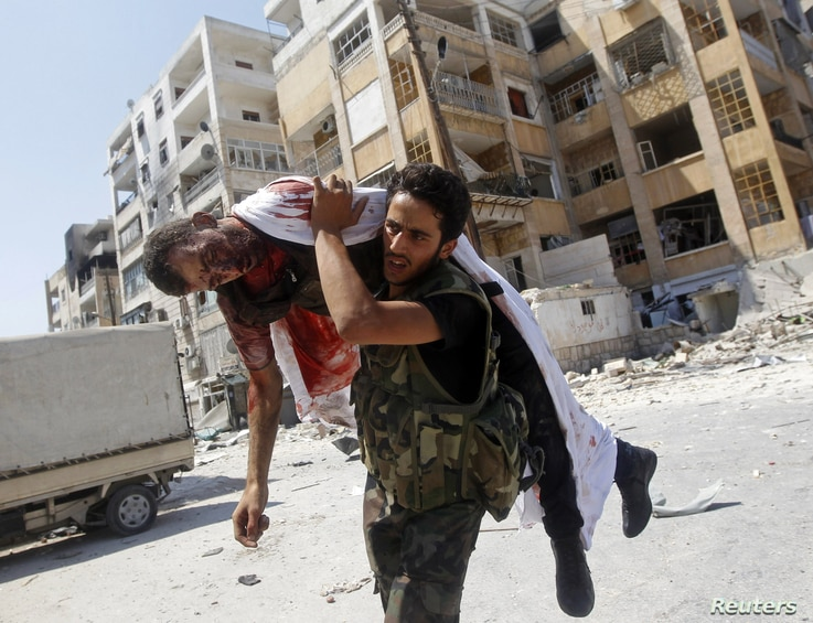 Free Syrian Army fighter carries body of fellow fighter during clashes in Aleppo, August 16, 2012.