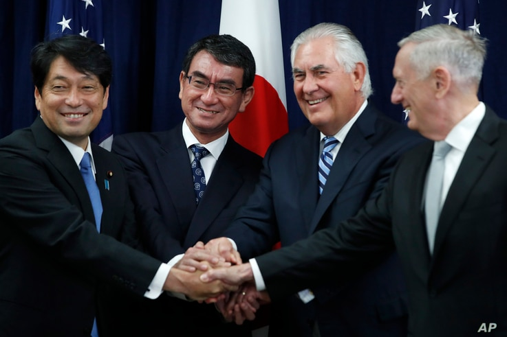 "From left, Japanese Defense Minister Itsunori Onodera, Japanese Foreign Minister Taro Kono, Secretary of State Rex Tillerson and Defense Secretary James Mattis shake hands ""ASEAN style"" at the start of a Security Consultative Committee meeting at the..."
