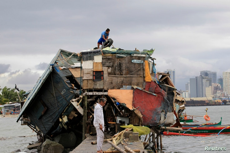 A man works on the roof of his house beside a damaged house after Typhoon Rammasun battered a coastal area of Baseco compound, metro Manila, July 17, 2014.