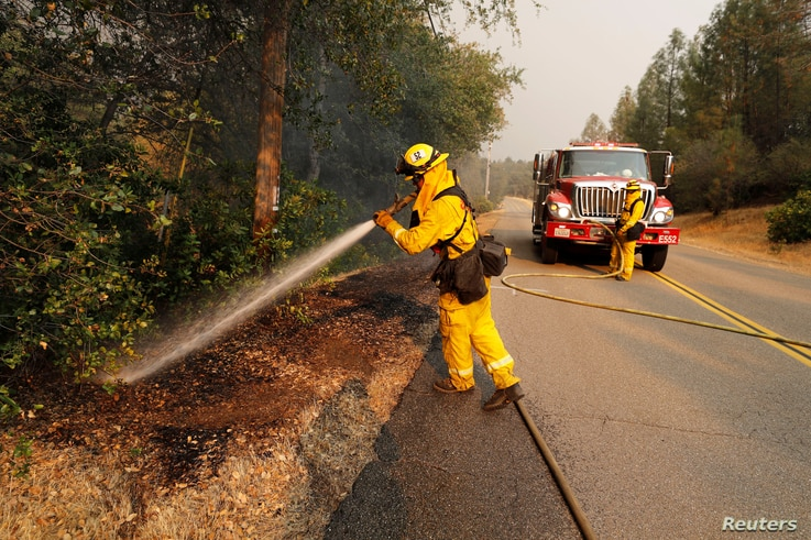 A firefighter knocks down a hot spot while working to stop the spread of the Carr Fire, west of Redding, Calif., July 27, 2018.