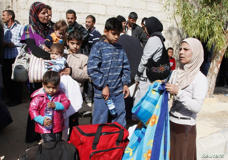 FILE - Syrian families leave the besieged town of Moadamiyeh, a Damascus suburb, Oct. 29, 2013.