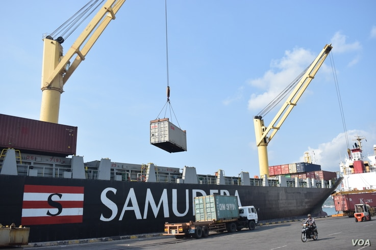 Containers being loaded onto a ship at Sihanoukville port. (D. de Carteret/VOA)