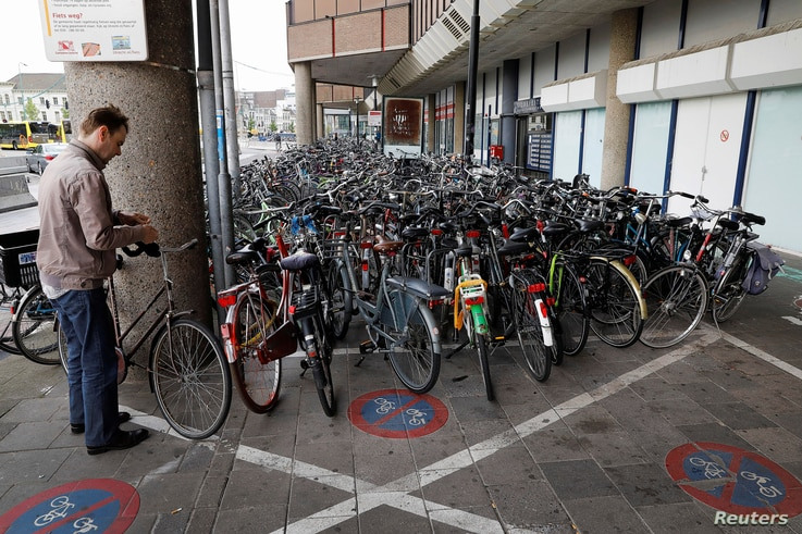 A cyclist parks his bike on the street near the world's largest bike parking garage in Utrecht, Netherlands Aug. 21, 2017.