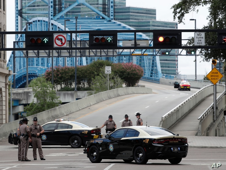 Florida Highway patrolmen block the entrance to the Main Street Bridge near the scene of a mass shooting at Jacksonville Landing in Jacksonville, Fla., Sunday, Aug. 26, 2018. Florida authorities are reporting multiple fatalities at the riverfront mal...
