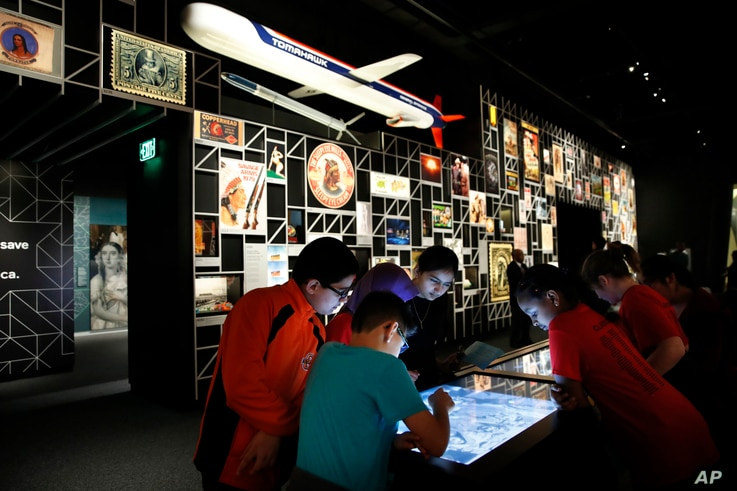 """A school groups explores an interactive touch table to learn about the objects and images on display at the """"Americans"""" exhibit at the Smithsonian's National Museum of the American Indian in Washington, Feb. 9, 2018."""