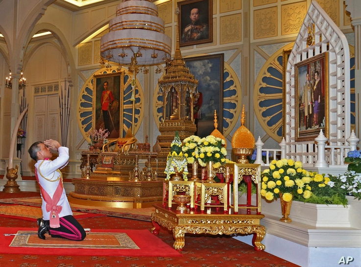 In this photo released by Bureau of the Royal Household, Thailand 's new king Maha Vajiralongkorn Bodindradebayavarangkun pays his  respects to a portrait of the late Thai King Bhumibol Adulyadej and Thai Queen Sirikit  at the Dusit Palace Dec.1, 201