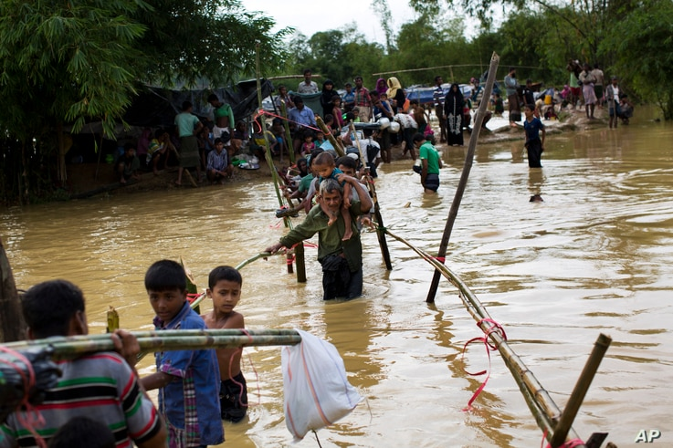 Rohingya Muslims cross a flooded area to find an alternate shelter after their camp was inundated with rainwater near Balukhali refugee camp, Bangladesh, Sept. 19, 2017.