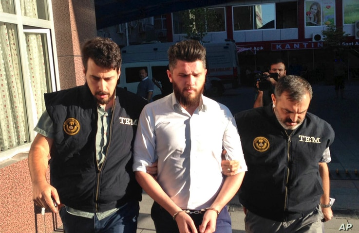 Turkish police officers escort a man arrested in a raid in Konya, Turkey, July 12, 2017. Police killed five Islamic State militants in a firefight that erupted during a raid on a house in the central city of Konya, officials said.