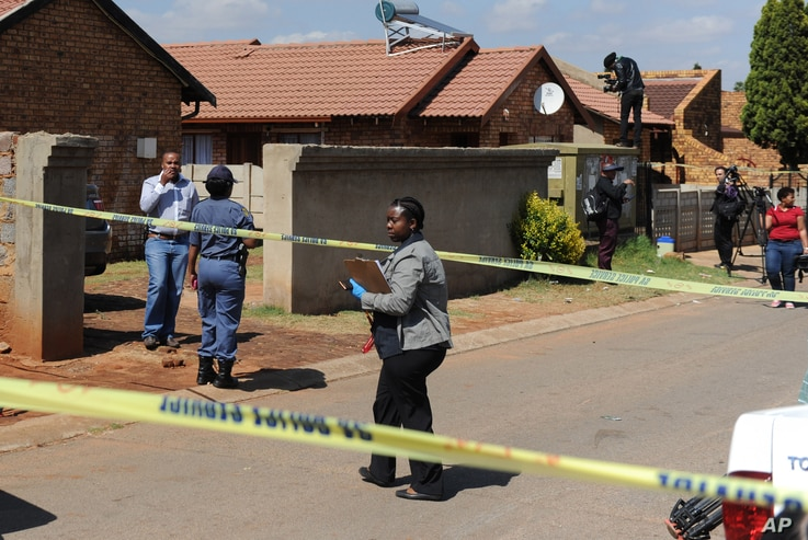 Police, forensic investigators and press  work outside the home of actress and singer, Kelly Khumalo, in Vosloorus, east of Johannesburg, Monday Oct. 27, 2014.