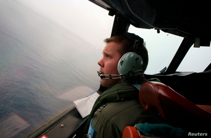 Co-Pilot, Flying Officer Marc Smith, turns his Royal Australian Air Force (RAAF) AP-3C Orion aircraft at low level in bad weather whilst searching for the missing Malaysian Airlines Flight MH370 over the southern Indian Ocean, March 24, 2014.