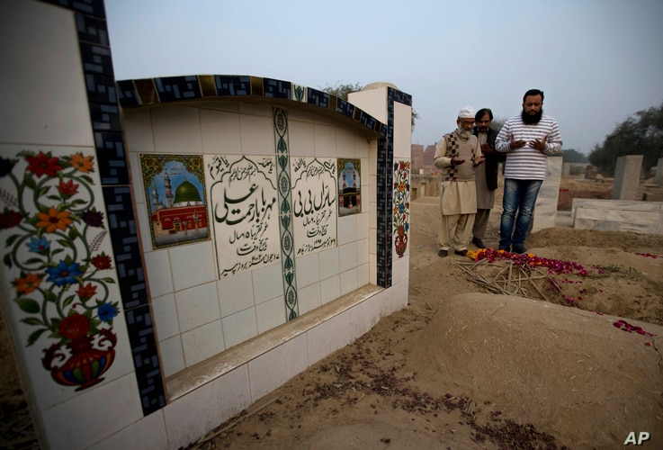 Mohammed Amin, left, offer prayers at a grave of his seven year-old daughter Zainab Ansari in Kasur, Pakistan, Jan. 18, 2018.