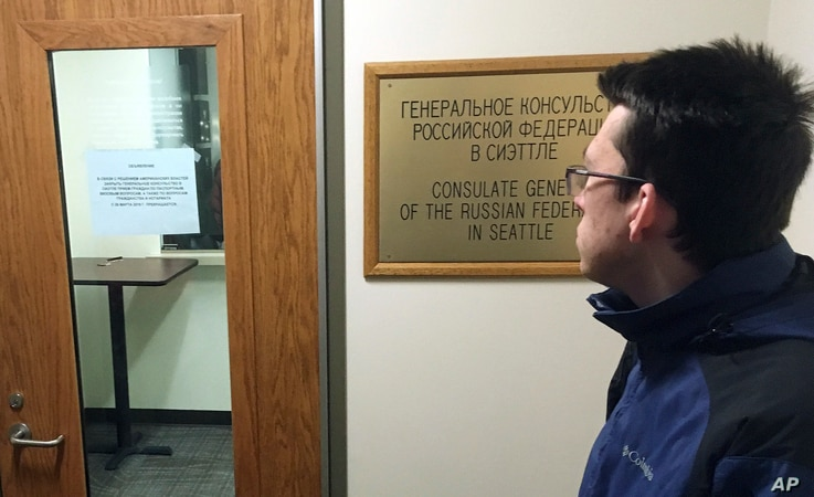 A person, who refused to give their name, checks a sign on the door of the Russian consulate office stating that the office is closed and not accepting any new passport applications in Seattle, Washington, March 26, 2018.