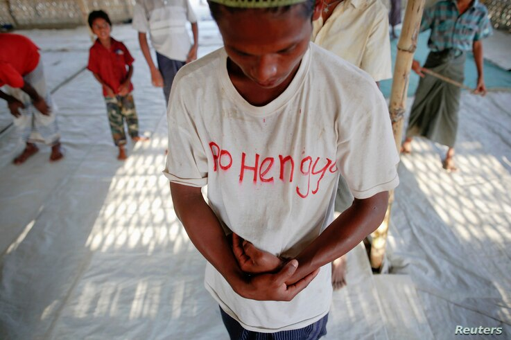 """A Rohingya Muslim with the word """"Rohingya"""" written on his T-shirt prays with others at a makeshift mosque at a camp for those displaced by violence, near Sittwe April 28, 2013."""