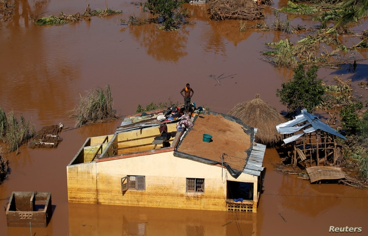 A man looks around from atop his house after Cyclone Idai in Buzi district outside Beira, Mozambique, March 22, 2019.