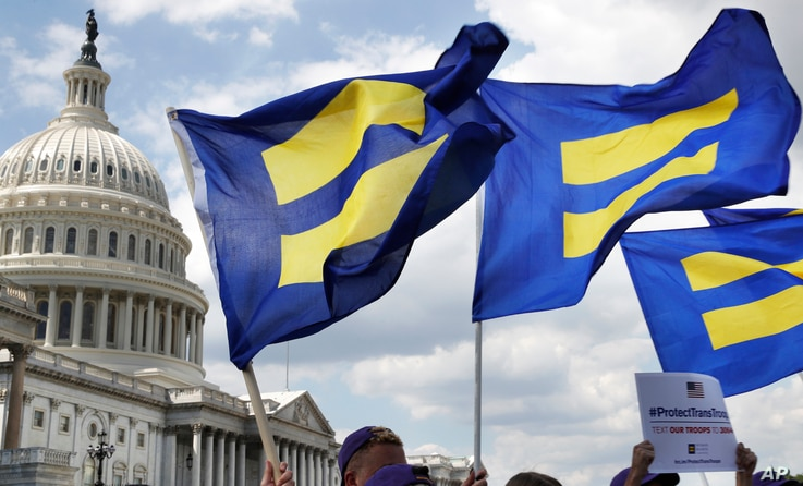 "FILE - In this July 26, 2017, photo, people with the Human Rights Campaign hold up ""equality flags"" during an event on Capitol Hill in Washington, in support of transgender members of the military."