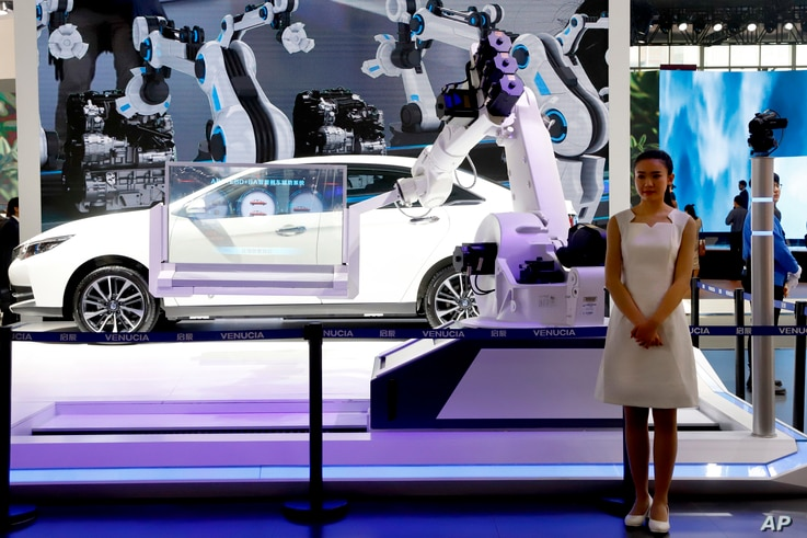 FILE - An industrial robot is displayed with a car at the booth of a Chinese automaker during the China Auto 2018 show in Beijing, China, April 26, 2018.