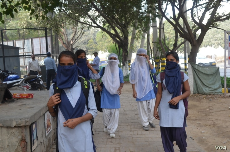 School students try to protect themselves from the dirty air in Delhi, Nov. 8, 2017. (A. Pasricha/VOA)