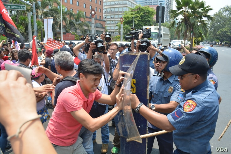 Youth militant leader Vencer Crisostomo pushes against a police shield to get closer to the U.S. embassy in Manila ahead of President Barrack Obama's visit to the Philippines, April 23, 2014. (Simone Orendain/VOA)