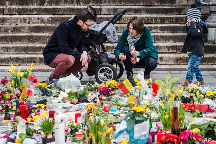 A family lights a candle at a memorial site at the Place de la Bourse in Brussels, March 27, 2016.