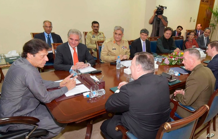 In this photo released by Pakistan's Press Information Department, Pakistan's Prime Minister Imran Khan, left, meets with visiting U.S. Secretary of State Mike Pompeo, front, in Islamabad, Pakistan, Sept. 5, 2018.