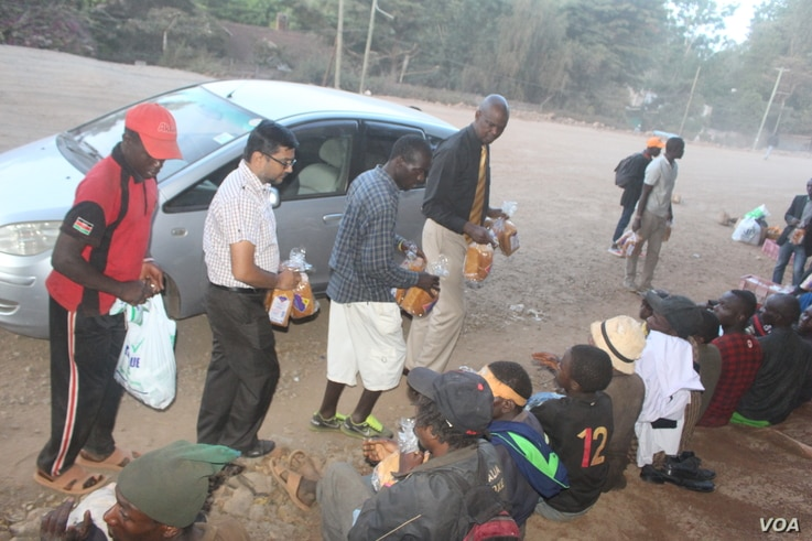 Clifford Oluoch (right) distributes bread to homeless children with the help of volunteers. (VOA/Rael Ombuor)