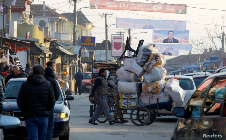 A vendor pushes a wheelbarrow under electoral posters in Suto Orizari, a district with Europe's largest Roma communities, Macedonia, Dec. 7, 2016.