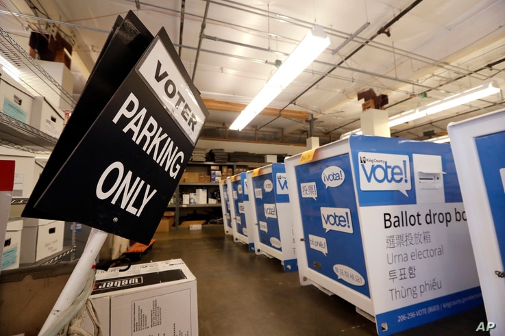 FILE - Ballot drop boxes are stored with other voting equipment in a warehouse portion of the King County elections office in Renton, Wash., Sept. 19, 2018.