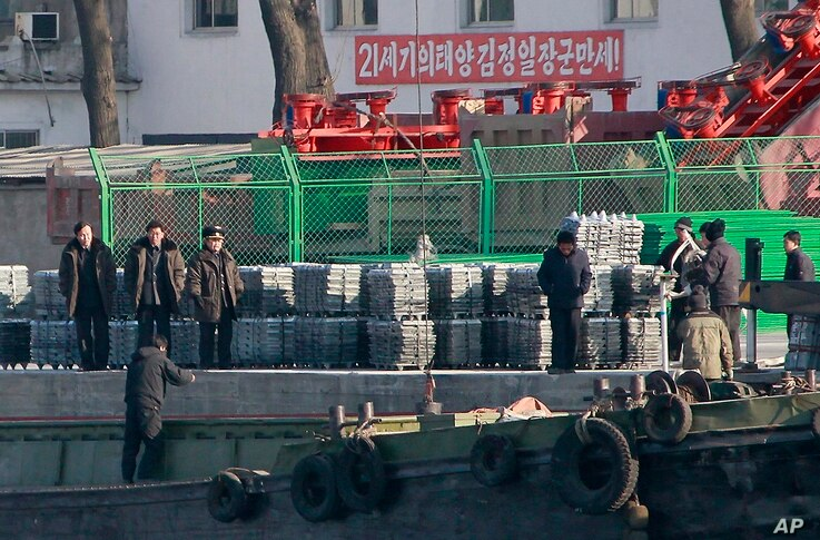 FILE - North Korean men unload goods off a boat on the river bank of the North Korean town of Sinuiju, opposite side of Chinese city of Dandong bordering with North Korea, Dec. 30, 2011.