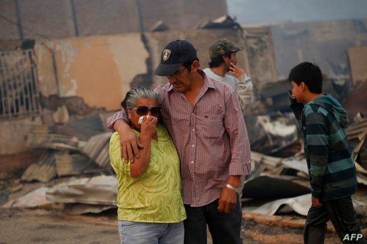 A crying woman is comforted amid the remains of a burnt-down house after a forest fire devastated Santa Olga, 240 kilometers south of Santiago, Chile, Jan. 26, 2017.