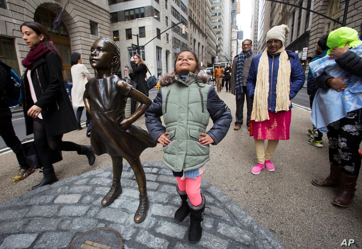"""Shriya Gupta of Cherokee, N.C. strikes a pose with a statue titled """"Fearless Girl"""", Wednesday, March 8, 2017, in New York. The statue was installed by an investment firm in honor of International Women's Day."""