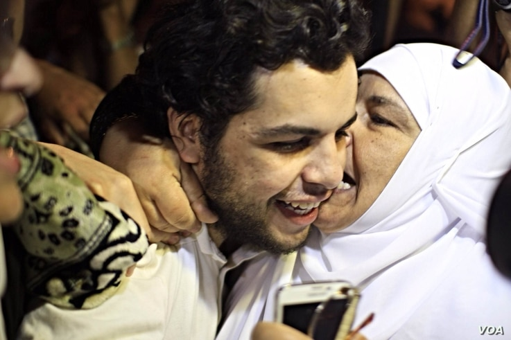 Al-Jazeera Arabic service reporter Abdullah Elshamy is greeted by friends and family after being released from a Cairo prison Tuesday evening, June 17, 2014. (VOA / Hamada Elrasam)