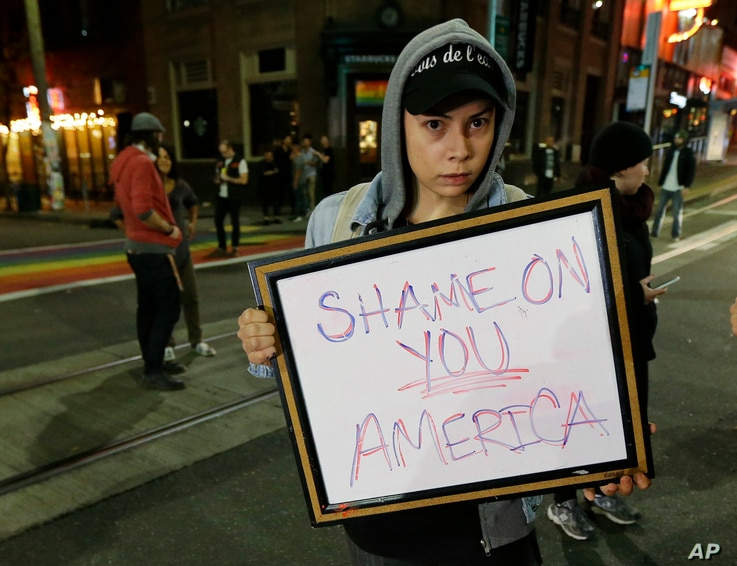 "Felomina Cervantes, of Seattle, holds a sign that reads ""Shame on You America"" as she takes part in a protest against President-elect Donald Trump, Nov. 9, 2016, in Seattle's Capitol Hill neighborhood."