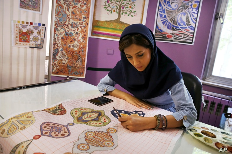 An Iranian woman sketches and paints carpet patterns at a workshop in the Cultural and Artistic Carpet Foundation of Rassam Arabzadeh in Tehran, Iran, Aug. 4, 2015.