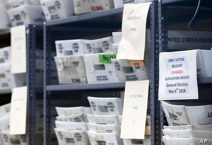 Bins filled with ballots are stacked at the Broward County Supervisor of Elections office as employees count ballots during a recount in Lauderhill, Florida, Nov. 14, 2018.