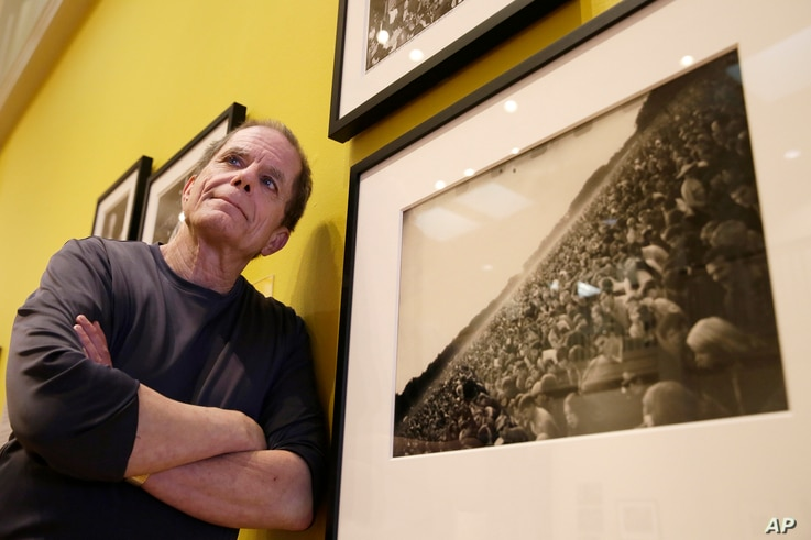 """In this Wednesday, May 10, 2017 photo, curator Dennis McNally stands by a photograph of the """"Human Be-In"""" at the exhibit """"On the Road to the Summer of Love"""" in the California Historical Society in San Francisco. McNally, who curated the exhibit, unco..."""