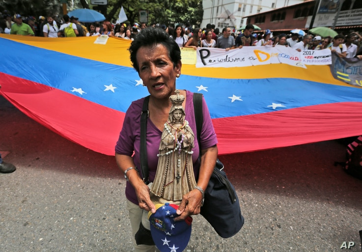 A woman holds a Virgin Mary statue during a protest march during a protest march against Venezuela's President Nicolas Maduro's government and also to commemorate the country's Day of the Journalist, in Caracas, Venezuela, June 27, 2017.