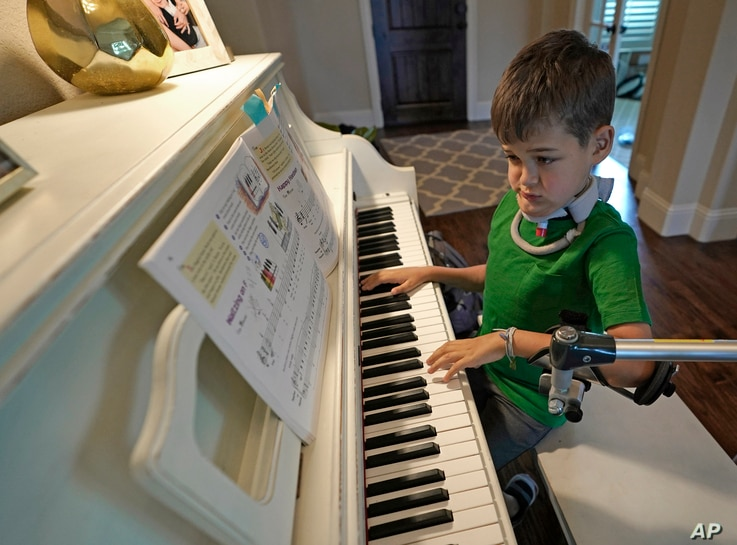 Braden Scott uses a device to support his left arm as he practices on the piano in Tomball, Texas, March 29, 2019. Braden was diagnosed with the syndrome called acute flaccid myelitis, or AFM, in 2016 and was paralyzed almost completely.