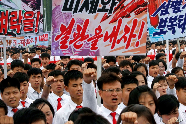 """Tens of thousands of men and women pump their fists and chant as they carry placards with anti-American propaganda slogans at Pyongyang's central Kim Il Sung Square, June 25, 2017, to mark what North Korea calls """"the day of struggle against U.S. impe..."""