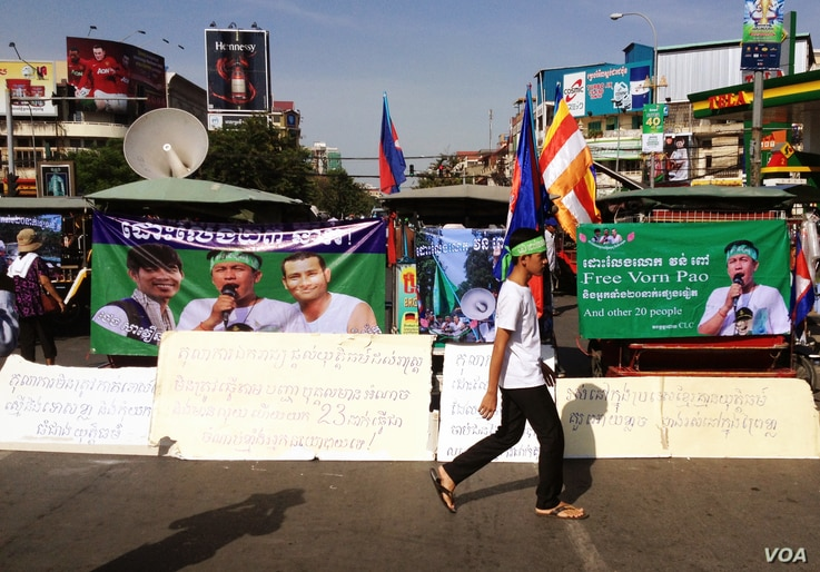 A supporter walks in front of a row of motorized rickshaws covered with banners supporting the 23 defendants in Phnom Penh, Cambodia, May 30, 2014. (Robert Carmichael/VOA)