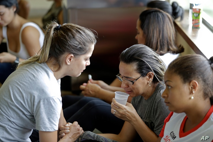 A woman is comforted by a volunteer as she waits for informations about missing relatives, after a dam collapsed in Brumadinho, Brazil, Jan. 26, 2019. The Brazilian mining company Vale SA CEO Fabio Schvartsman said he did not know what caused the col...