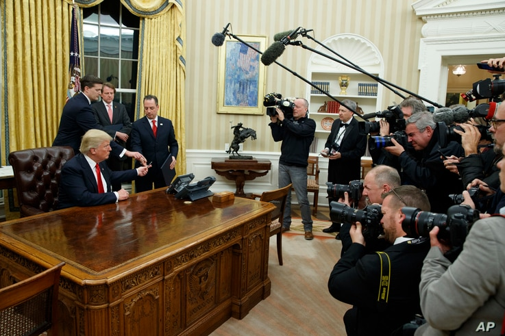 FILE - President Donald Trump hands over his pen after signing his first executive order in the Oval Office of the White House in Washington, Jan. 20, 2017. Emoluments have figured prominently in discussions about the new president and his administra...