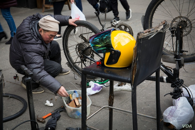 Zheng, a Chinese delivery worker, repairs his bike on a New York sidewalk.