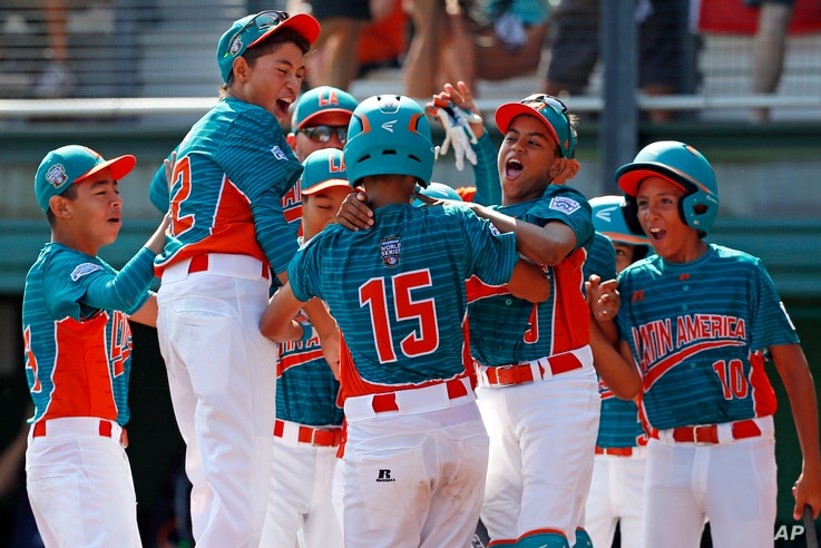 Maracaibo, Venezuela's Jonney Rosario (15) celebrates with teammates after hitting a two-run home run during the first inning of an International pool play baseball game against White Rock, British Columbia.