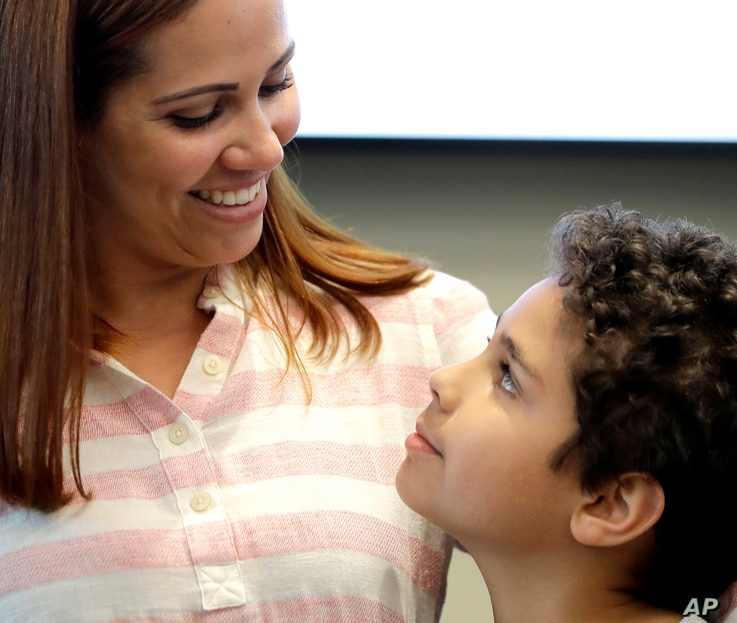 Lidia Karine Souza and her son Diogo De Olivera Filho smile at each other at the Mayer Brown law firm during a news conference shortly after Diogo was reunited with his mother, June 28, 2018, in Chicago. Federal judge Manish Shah earlier today ordere...