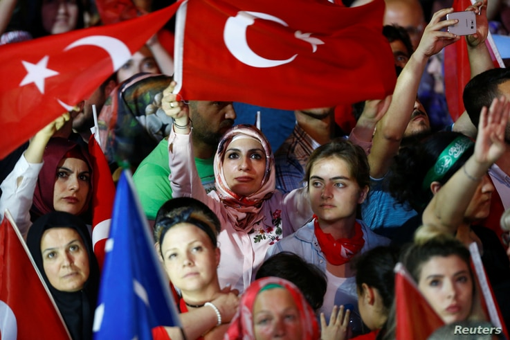 People wave Turkey's national flags as they attend a ceremony marking the first anniversary of the attempted coup in front of the Turkish Parliament in Ankara, July 16, 2017.