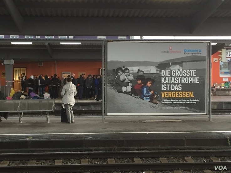 """Migrants await their fate at Freilassing's train station in Germany near a billboard by charity groups urging Germans to support refugees.  It reads:  """"The biggest catastrophe is forgetting.   12 million people from Syria and Iraq are fleeing. We mus..."""