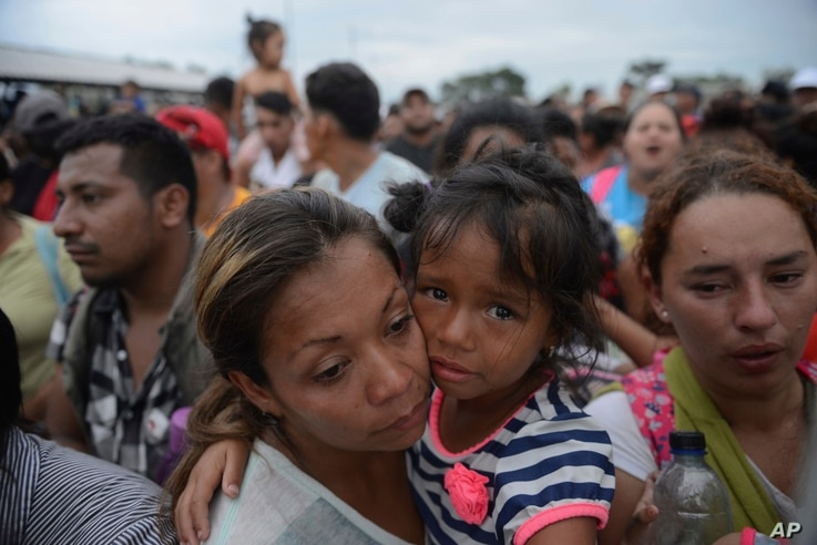 Migrants bound for the U.S.-Mexico border wait on a bridge that stretches over the Suchiate River, connecting Guatemala and Mexico, in Tecun Uman, Guatemala, Oct. 19, 2018.